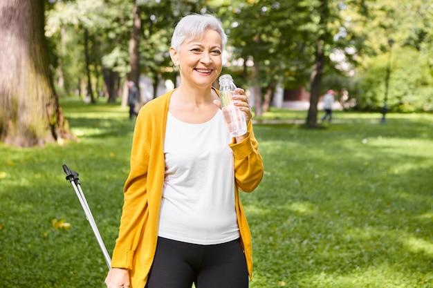 Ritratto di attraente donna senior in buona salute con capelli grigi pixie riposando mentre si cammina nel parco utilizzando i poli scandinavi nordici, tenendo la bottiglia, acqua potabile, sentendosi pieni di energia, sorridente Foto Gratuite