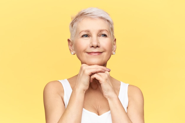 Portrait of attractive joyful middle aged woman with short stylish haircut and tanned skin placing hands under chin, doing anti aging face lifting massage. Free Photo