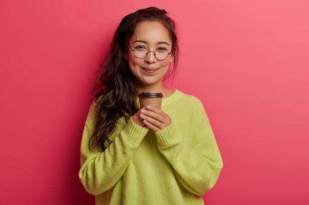Il ritratto della ragazza coreana attraente sta con il caffè da asporto, gode della bevanda della caffeina, guarda con l'espressione felice tenera Foto Gratuite
