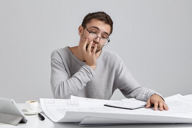 Ritratto di uomo attraente indossa occhiali rotondi, sembra perplesso nei progetti, non ha idea di come disegnare schizzi Foto Gratuite