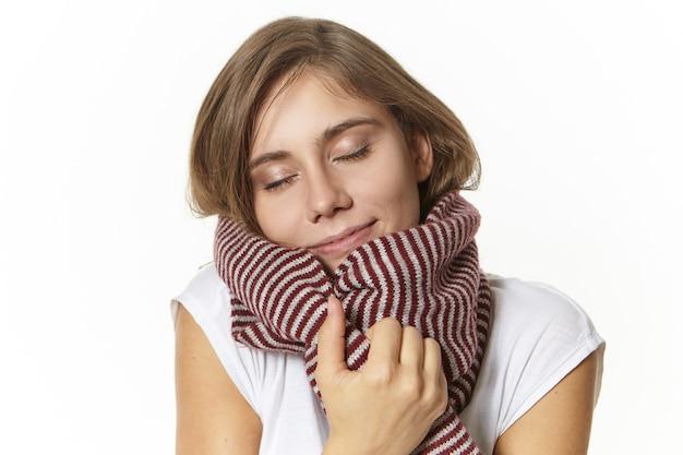 Ritratto di attraente e soddisfatta giovane femmina europea con trucco naturale chiudendo gli occhi e sorridendo con gioia, godendo di una morbida sciarpa di lana, riscaldandosi nella fredda giornata invernale Foto Gratuite