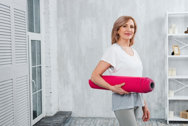 Portrait of a attractive senior woman holding pink mat in hand at home Free Photo