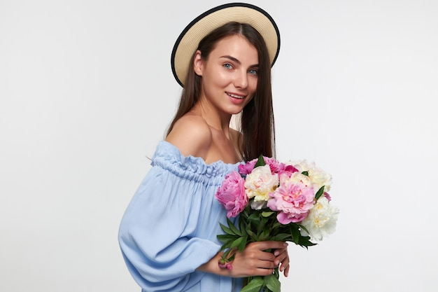 Portrait of attractive, smiling girl with long brunette hair. wearing a hat and blue pretty dress. holding a bouquet of beautiful flowers. watching  isolated over white wall Free Photo