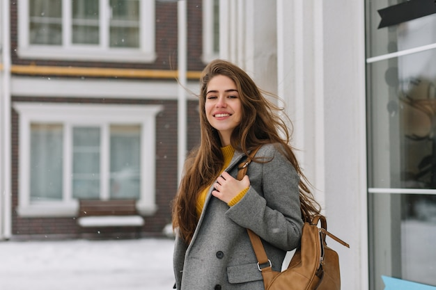 Portrait of attractive woman with long brown hair carrying backpack and gently smile. photo of refined caucasian lady in gray jacket posing Free Photo
