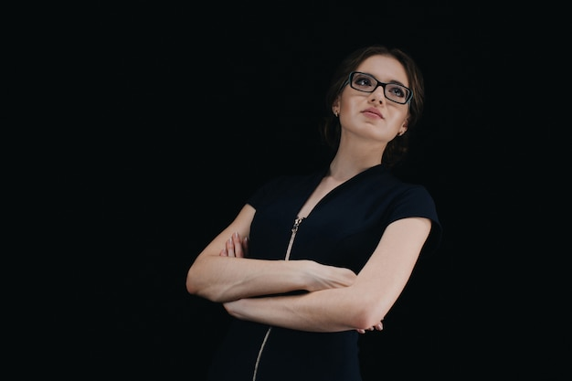 Portrait of attractive young caucasian business woman with crossed arms on black Premium Photo