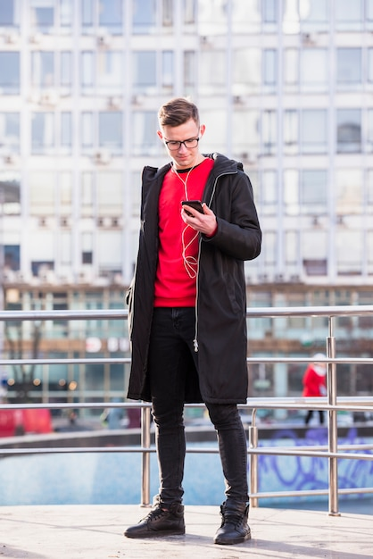 Portrait of an attractive young man wearing long jacket listening music on cellphone Free Photo