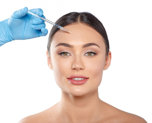 Portrait of an attractive young woman receiving botox treatment. Premium Photo