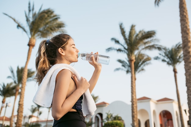 Portrait attractive young woman in sportswear drinking water from bottle on palms and sky. tropical city, sunny morning, relaxing with closed eyes, workout. Free Photo