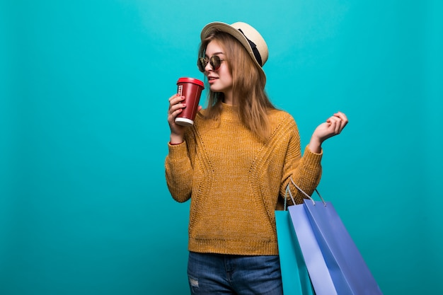 Portrait of attractive young woman with shopping bags and paper cup of fresh coffee Free Photo