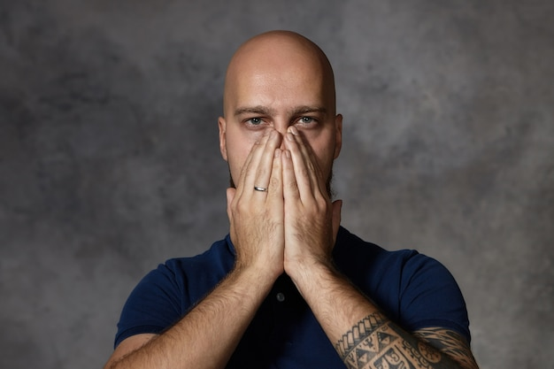 Ritratto di uomo attraente con il tatuaggio che copre la bocca e il naso con entrambe le mani, trattenendo il respiro a causa del cattivo odore. maschio frustrato esausto stanco in posa in stduio, tenendo le mani sul viso Foto Gratuite