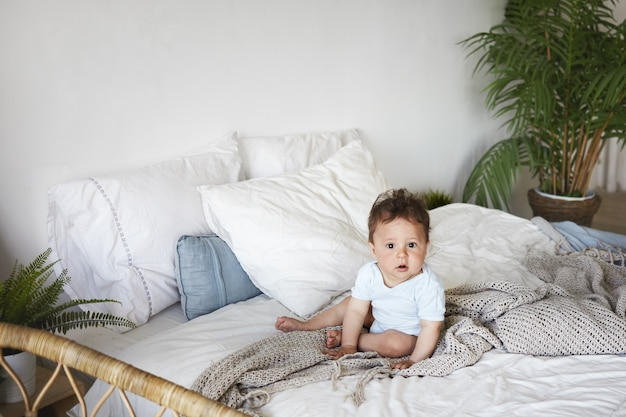 A portrait baby boy sitting upright on the bed Free Photo