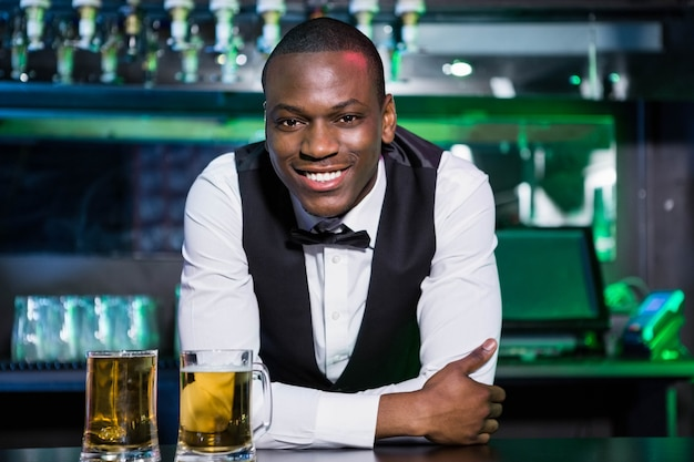 Portrait of bartender leaning and smiling on bar counter with two glasses of beer in front of him Premium Photo
