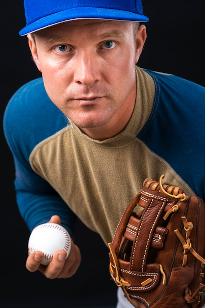Portrait of baseball player holding ball and glove Free Photo