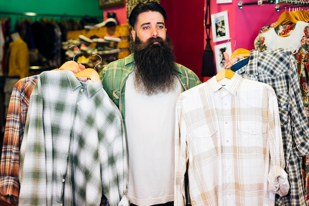 Portrait of bearded man holding shirts in the coat hanger Free Photo