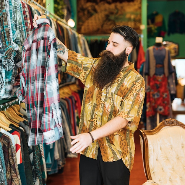 Portrait of a bearded man looking at plaid shirt in clothing shop Free Photo