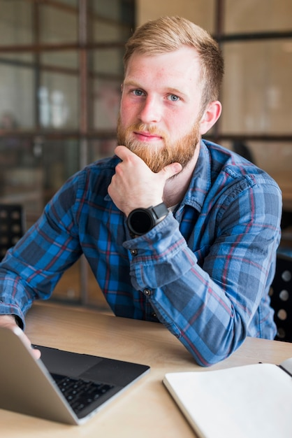 Portrait of bearded man sitting in front of laptop at workplace Free Photo