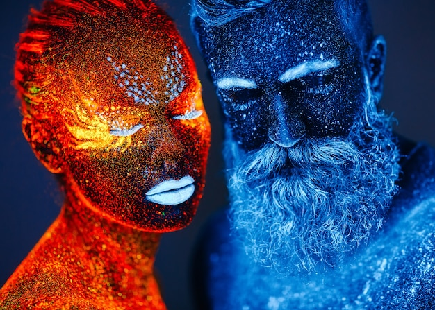 Portrait of a bearded man and woman painted in ultraviolet powder. Premium Photo