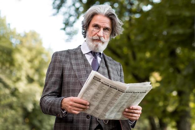 Portrait of bearded mature male reading newspaper Free Photo