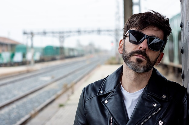 Portrait of a bearded rocker with sunglasses on an abandoned train station Premium Photo