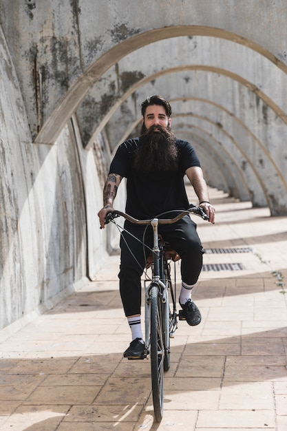 Portrait of a bearded young man riding the bicycle in arches Free Photo