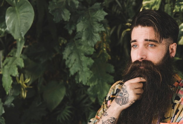 Portrait of a bearded young man standing in front of leaves Free Photo