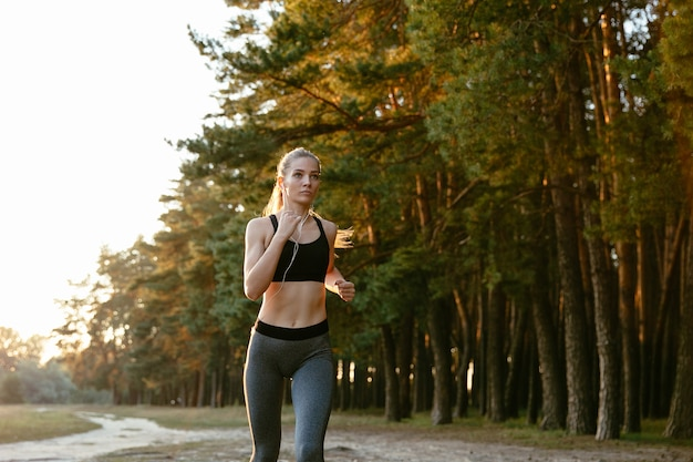 Portrait of beautiful active woman in headset jogging in the wood, listening to music. Free Photo