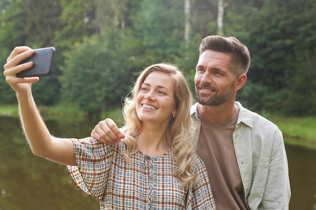 Portrait of beautiful adult couple taking selfie while posing by lake in green countryside scenery Premium Photo