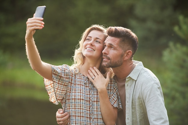 Portrait of beautiful adult couple taking selfie with engagement ring after marriage proposal during romantic date outdoors Premium Photo