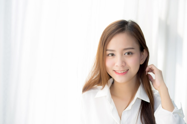 Portrait of beautiful asian woman standing the window and smile while wake up. Premium Photo
