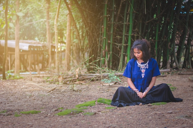 Portrait of beautiful asian woman with local dress, sitting under bamboo tree with peace in mind, in Premium Photo
