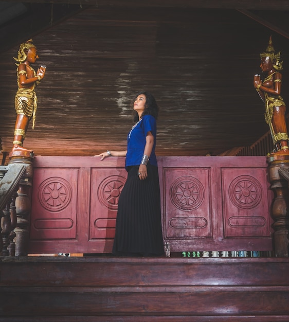 Portrait of beautiful asian woman with local dress, standing in public temple at countryside of thai Premium Photo