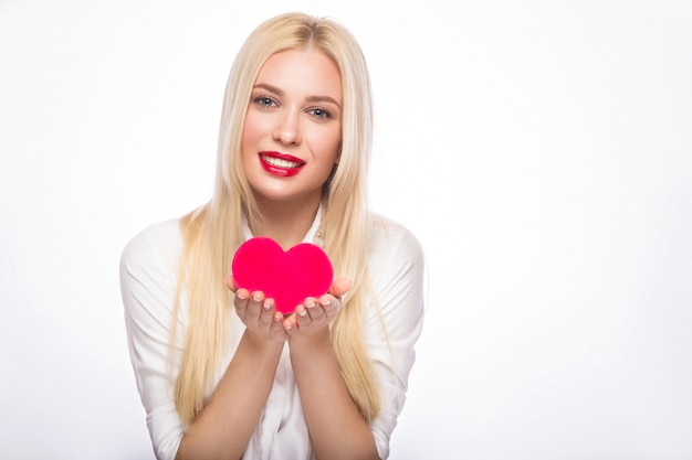 Portrait of beautiful blond woman with bright makeup and red heart in hand Premium Photo