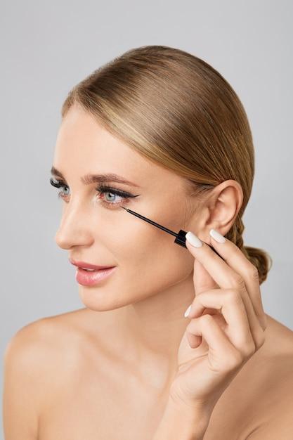 Portrait of beautiful blonde woman applying liquid eyeliner with brush. natural make up. Premium Photo