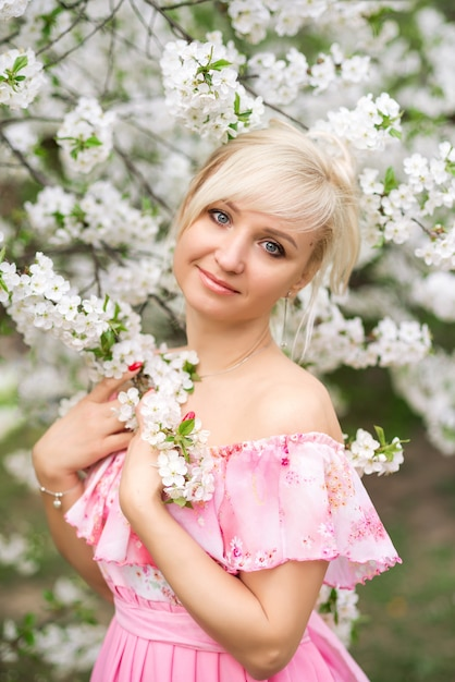 Portrait of a beautiful blonde woman in a pink dress in a blooming garden in spring. Premium Photo