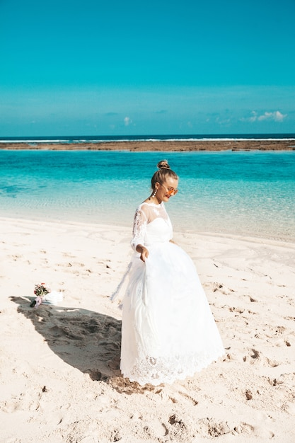 Portrait of  beautiful bride dancing on the beach behind blue sky and sea Free Photo