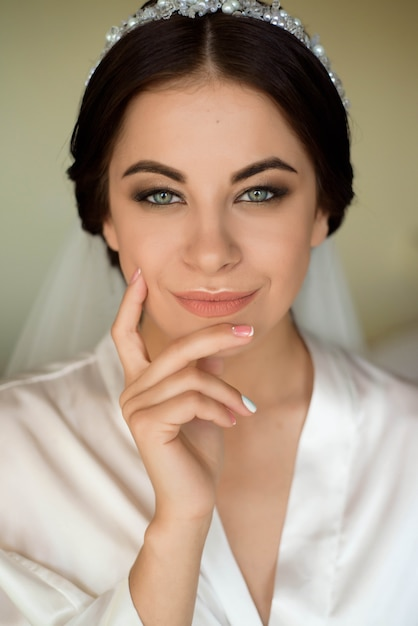 Portrait of beautiful bride with fashion veil posing on bed at wedding morning. makeup. brunette girl. wedding veil. Premium Photo