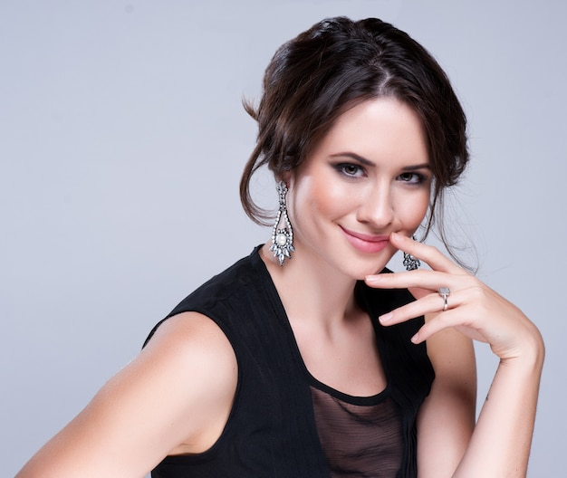 Portrait of beautiful brunette woman in black dress. cosmetic eyeshadows. Premium Photo