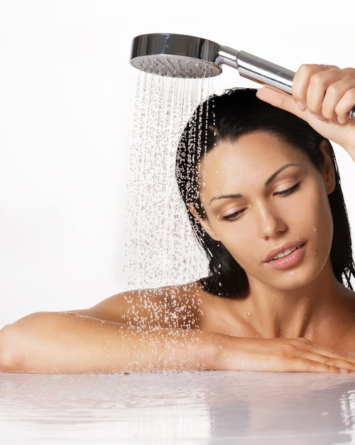 Ritratto di una bella donna bruna tiene la doccia in mano con acqua che cade Foto Gratuite
