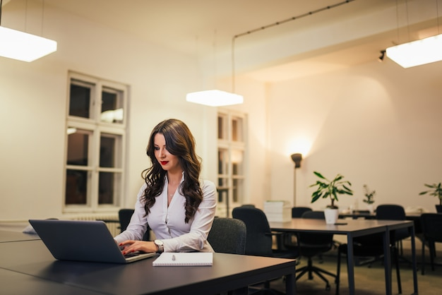 Portrait of beautiful businesswoman with red lipstick sitting at workplace in modern office Premium Photo