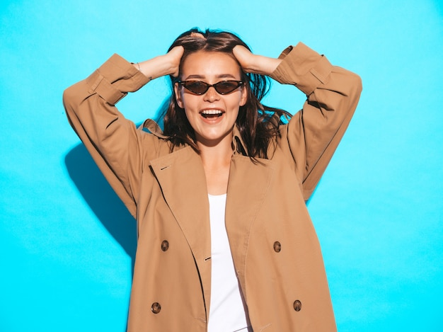 Portrait of beautiful caucasian brunette woman model in brown overcoat and sunglasses.girl posing near blue wall Free Photo