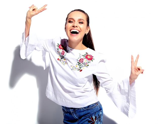 Portrait of beautiful caucasian smiling brunette woman model in white blouse and summer stylish blue jeans with flowers print Free Photo
