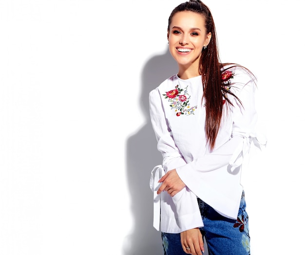 Portrait of beautiful caucasian smiling brunette woman model in white blouse and summer stylish blue jeans Free Photo