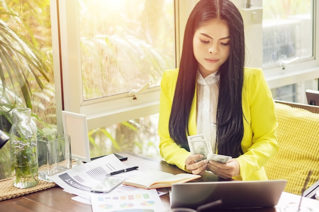Portrait of beautiful and confident asian business woman in working with notebook laptop and book manage job work at workplace. Premium Photo