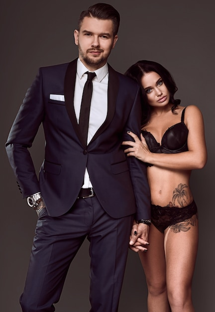 Portrait of a beautiful couple: brutal man in elegant suit and sexy girl with a tattoo in lingerie on gray background Premium Photo
