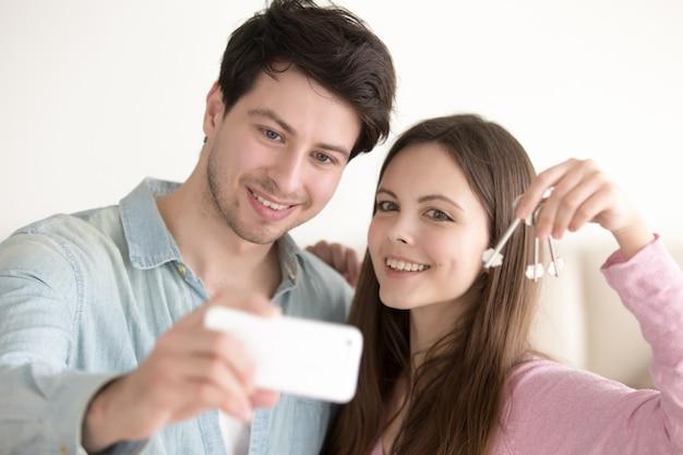 Portrait of beautiful couple making selfie on mobile holding key Free Photo