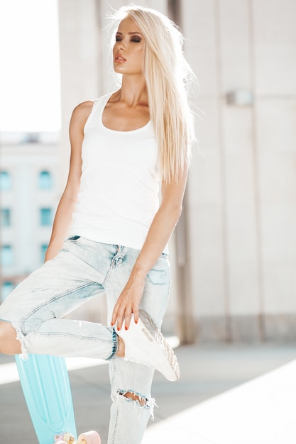 Portrait of beautiful cute blond girl in white t-shirt and jeans posing outdoors. girl with blue penny skateboard  on the street Free Photo