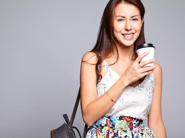 Модель женщины брюнет портрета красивая милая в расчалках и вскользь одеждах лета без состава изолированного на сером цвете. пить свежий кофе Бесплатные Фотографии