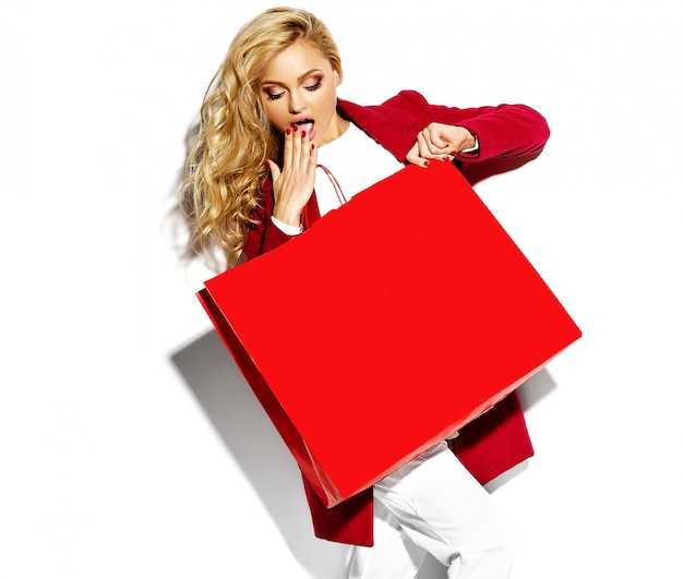 Portrait of beautiful cute happy sweet surprised blonde woman girl holding in her hands big shopping bag in hipster red clothes isolated on white Free Photo