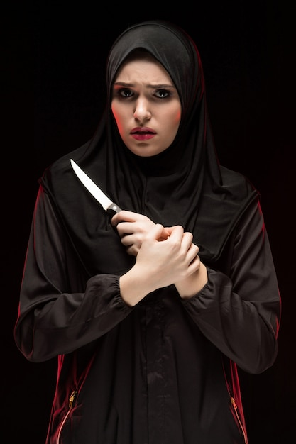 Portrait of beautiful desperate scared frightened young muslim woman wearing black hijab holding knife in her hands Premium Photo