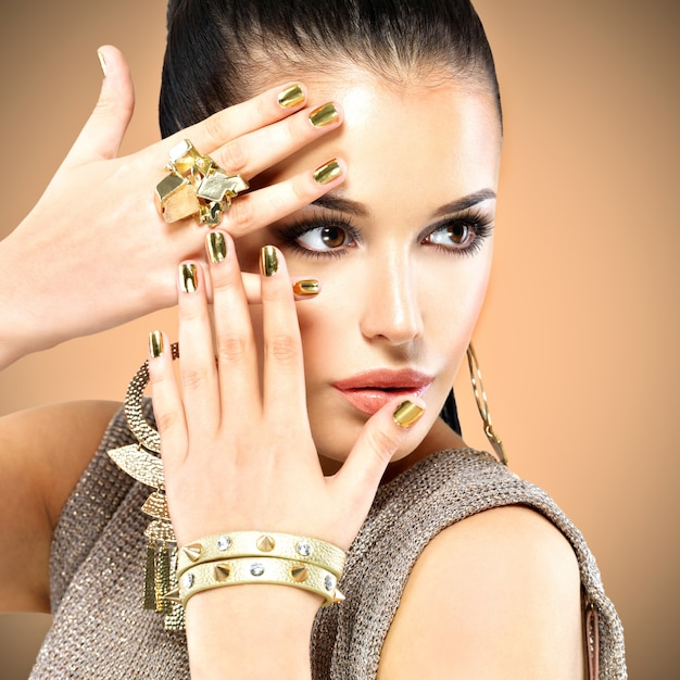Portrait of the beautiful fashion woman with black makeup and golden manicure Free Photo